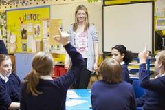 Elever för lärareTeaching Lesson To grundskola royaltyfri foto