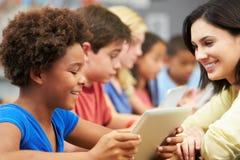 Elever i grupp som använder den Digital minnestavlan med läraren Royaltyfri Bild
