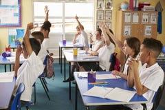 Elever lyfter händer i en kurs på grundskola för barn mellan 5 och 11 år, sidosikt arkivfoto