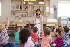 Elever på den Montessori skolan som lyfter händer för att svara fråga royaltyfri fotografi