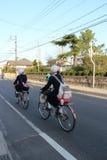 Elever rider deras cykel i en gata av Matsue (Japan) Royaltyfri Foto
