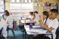 Elever som använder minnestavladatorer i grupp på en grundskola för barn mellan 5 och 11 år Royaltyfri Bild