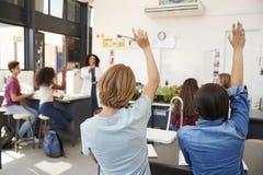 Elever som lyfter händer i en högstadiumvetenskapskurs arkivfoton