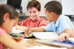 Elever som studerar på skrivbord i klassrum Arkivbild