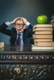 Elevpojke i spänning eller fördjupning på skolaklassrumet Arkivfoton