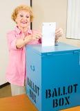 Elezione - la donna maggiore lancia la scheda elettorale Fotografia Stock Libera da Diritti