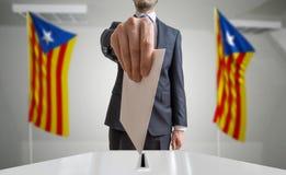 Elezione o referendum in Catalogna L'elettore tiene il voto di cui sopra disponibile della busta Bandiere della Catalogna nel fon fotografia stock