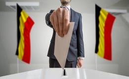 Elezione o referendum nel Belgio L'elettore tiene il voto di cui sopra disponibile della busta Bandiere belghe nel fondo fotografia stock libera da diritti