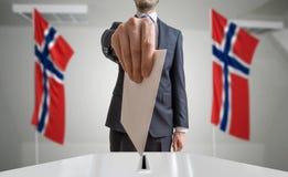 Elezione o referendum in Norvegia L'elettore tiene il voto di cui sopra disponibile della busta Bandiere norvegesi nel fondo fotografie stock