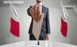 Elezione o referendum in Polonia L'elettore tiene il voto di cui sopra disponibile della busta Bandiere polacche nel fondo fotografia stock