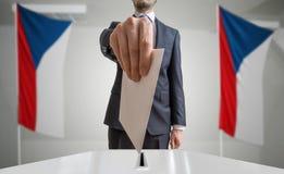 Elezione o referendum in repubblica Ceca L'elettore tiene il voto di cui sopra disponibile della busta Bandiere ceche nel fondo immagine stock libera da diritti