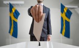 Elezione o referendum in Svezia L'elettore tiene il voto di cui sopra disponibile della busta Bandiere di Swedian nel fondo immagine stock libera da diritti