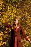 The elf in the autumn forest. The blonde girl in medieval red dress in the autumn forest Stock Photography