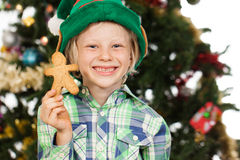 Elf boy holding gingerbread man Stock Photo