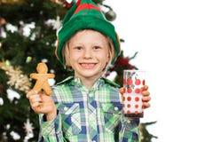 Elf chłopiec trzyma piernikowego mężczyzna i mleka Zdjęcie Royalty Free