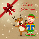 Elf & Funny Reindeer Christmas Card. Merry Christmas card with a cartoon reindeer smiling and greeting and a cute green elf holding a gift, with snow and a Stock Photo
