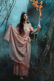 Elf girl in the fairy forest. She holds a staff in his hand Royalty Free Stock Photo