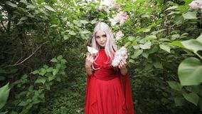Elf girl in a red dress stands in a spring garden. stock video footage