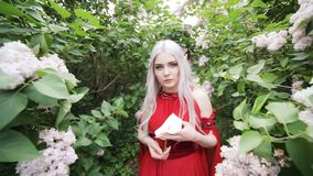 Elf girl in a red dress stands in a spring garden. stock footage