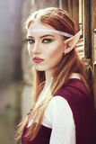 Elf girl. On the rock in red cloak posing outdoor stock photo