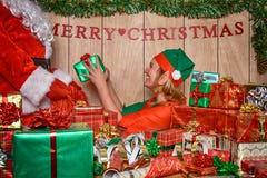 Elf het zetten stelt in de zak van de Kerstman voor Stock Afbeelding