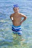 Elf Jahre alte Junge, die auf einem Felsen im Meer sitzen Lizenzfreies Stockbild
