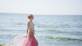 Elf princess like bird near sea, holds long light transparent flying fluttering train of gorgeous elegant pink dress. Lets fabric go to wind, slowly lowers stock footage