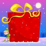 Elf pushing big Christmas gift Stock Image