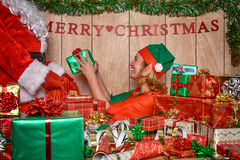 Elf puttings presents in Santa's sack Stock Image