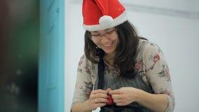 Elf is repairing wonderful toy to hang it on Christmas tree. stock video