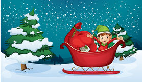 An elf riding on a sleigh with a sack of gifts Stock Photos