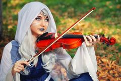 Elf with a violin in the autumn forest. Beautiful Girl In an elf costume playing a musical instrument Stock Image
