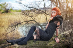 Elf woman with fiery hair on a log. Beautiful young fantasy style girl. Cosplay character stock images
