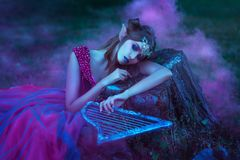 Elf woman in violet dress. Elf woman in purple dress with harp in hands royalty free stock images