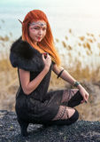 Elf women with fiery hair on nature. Elf woman with fiery hair on nature. Beautiful young fantasy girl. Cosplay character royalty free stock photo