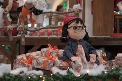 Elfe de Noël s'asseyant sur des cadeaux au centre commercial Images libres de droits