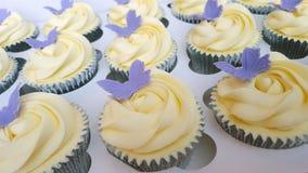 Elfenbein bereifte kleine Kuchen mit purpurroten Schmetterlingen Lizenzfreies Stockfoto