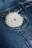 Elfenbeinblume broochon Denimhintergrund Lizenzfreies Stockfoto