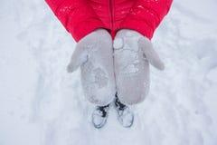 Elfenbeinfrauenhandschuhe im Schnee mit rotem Mantel Stockfotografie