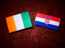Elfenbenskustenflagga med den kroatiska flaggan på en trädstubbe Fotografering för Bildbyråer