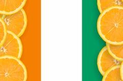 Elfenbenskustflagga i vertikal ram för citrusfruktskivor royaltyfri foto