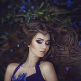 Elfenmädchen mit dem langen Haar in der Tiara steht im Frühjahr Waldblaue Waldblumen still Mädchen-Prinzessinträume Stockfotografie