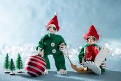 Elfes de sourire mignons d'aide de Santa tenant la babiole de Noël et un cadeau de Noël Scène de Noël de Pôle Nord Elfes au trava images stock