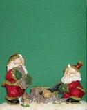 Elfi che tagliano legno sotto la neve Immagini Stock