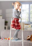 Elfish little girl on top of ladder at home Royalty Free Stock Photos