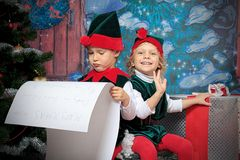 Elfs. Two cute children in christmas elf costumes posing over christmas background Stock Image
