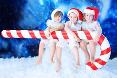 Elfs with candy. Beautiful little angelic children  with a huge candy at a christmas background Stock Photo
