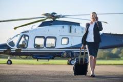 Elicottero di Walking Away From della donna di affari mentre parlando sulla calca fotografia stock