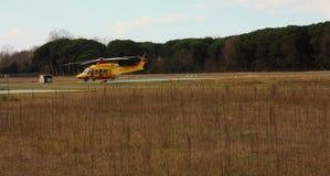 Elicottero giallo di salvataggio parcheggiato in un aeroporto locale immagine stock