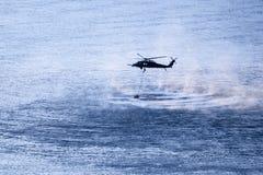 Elicottero militare che si libra sopra il fiume fotografia stock